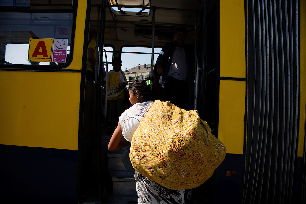 A Roma woman from the Nova Gazela settlement boards a Belgrade city bus with her family and possessions following the destruction of the camp.