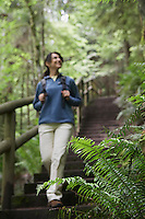 Middle aged woman on forest trail focus on fern in foreground