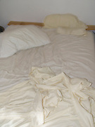unmade bed in the early morning with sunshine coming in
