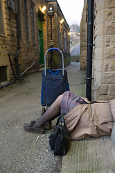 An elderly women collapsed in a doorway with her handbag