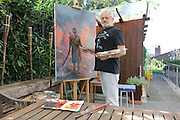Portrait of Grzegorz Rosinski, Polish comic book artist, born 1941 in Stalowa Wola, Poland, at work on a painting from the Thorgal series in his outdoor studio area on a verandah in his garden at his home in Mollens, Sierre, Switzerland, 9th September 2016. Rosinski is the author and designer of many Polish comic book series, and created Thorgal with Belgian writer Jean Van Hamme in 1977. The stories cover Norse mythology, Atlantean fantasy, science fiction, horror and adventure genres. Picture by Manuel Cohen