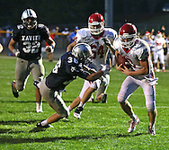Cedar Rapids Washington's Reid Snitker (3) spins away from Cedar Rapids Xavier's Ben Valentine (36) on an 11 yard touchdown run during their game at Xavier High School in Cedar Rapids on Friday, October 4, 2013. Washington defeated Xavier 26-10.