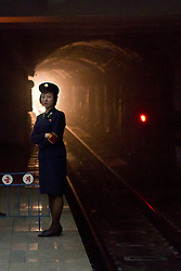 © Licensed to London News Pictures. 10/08/2011. Pyongyang, North Korea. A Pyongyang metro guard looks along the platform at a station as a train nears.  The Pyongyang metro is one of the deepest in the world, buried at around 100m below the city surface, every station doubles as a bomb shelter for citizens.  Photo credit : James Gourley/LNP/