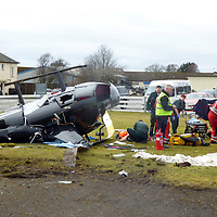 Helicopter Crash at Perth Airport, Scone….13.03.18<br />Paramedics from Scotland's Charity Air Ambulance (SCAA) treating the pilot of the Robinson helicopter which crashed shortly after 10.30am this morning at Perth Airport in Scone. The pilot was the only occupant and suffered non-life threatening injuries<br />Picture by Graeme Hart. <br />Copyright Perthshire Picture Agency<br />Tel: 01738 623350  Mobile: 07990 594431
