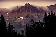 Clouds wrapped around peak on Going To The Sun Road at dusk