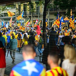 Hundreds of Catalans are reflected in a department store window wearing Catalan flags during the National Day of Catalonia.