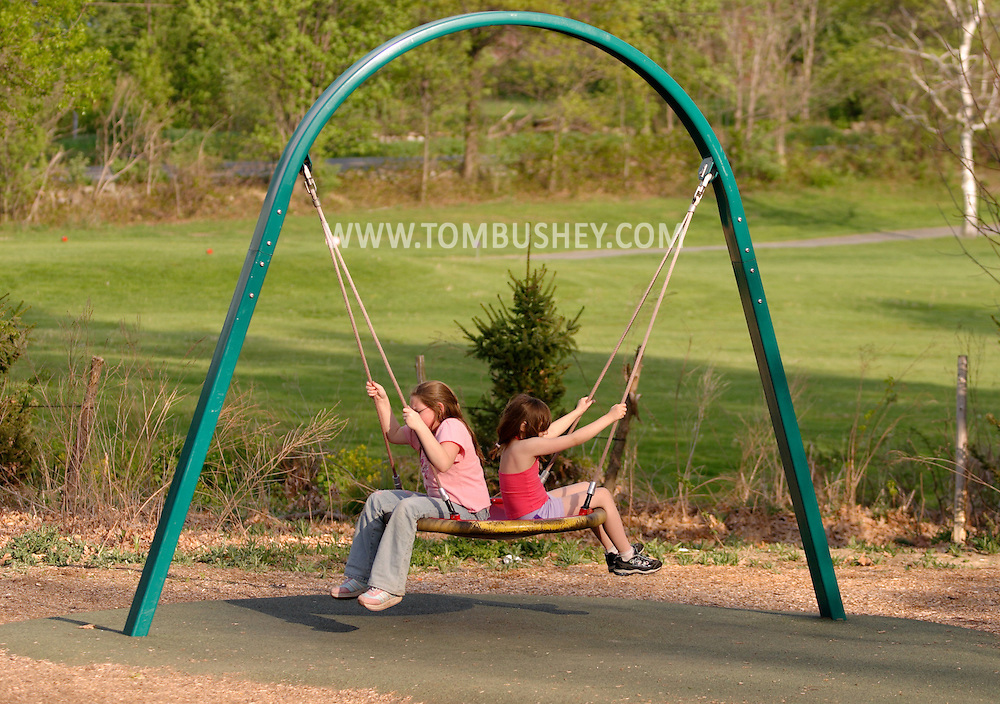 Hamptonburgh, N.Y. - A 9-year-old girl, left, and her 7-year-old sister sit on a swing at Thomas Bull Memorial Park on May 6, 2006. ©Tom Bushey, Model releases available.