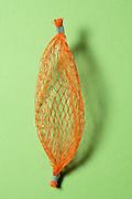 orange plastic fruit net against a green background