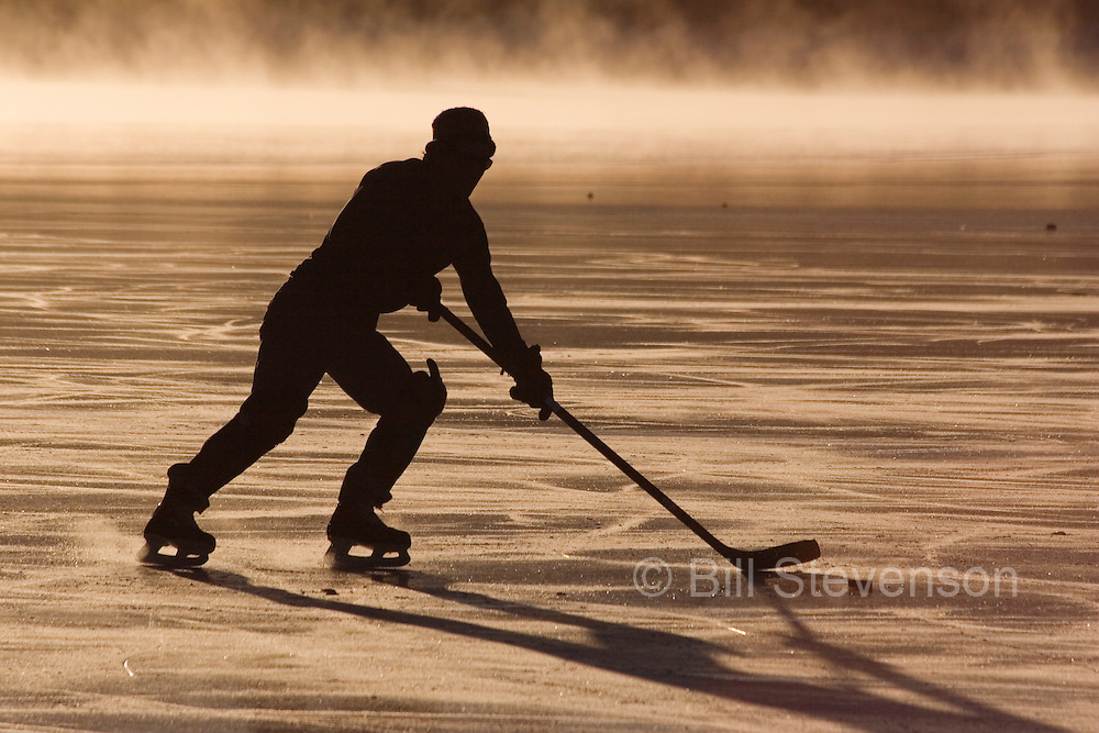 An image of an ice skater and mist on frozen Donner Lake California at sunrise