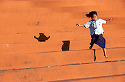 A child jumping down the bleachers is followed by her shadow while playing in the Chao Anouvong National Stadium in Vientiane, Laos.