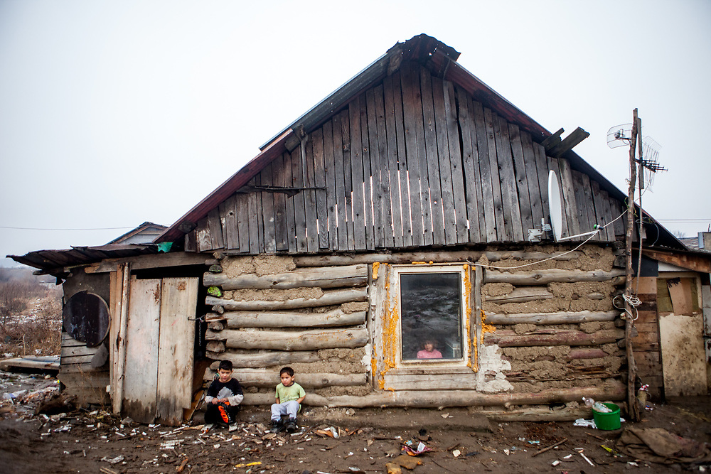 Children sitting in front of a house at the Roma settlement in Ostrovany.