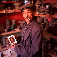 KASHGAR, 30 SEPTEMBER 2001: a Uighur antique dealer shows an old Mao Zedong bible .he says that Uighurs don't care for Chinese comunist relics as they were persecuted under Mao,but foreign tourists are ready to buy it.. . .(photo by: katharina hesse/Grazia Neri).
