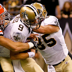 Oct 24, 2010; New Orleans, LA, USA; New Orleans Saints quarterback Drew Brees (9) is sacked by Cleveland Browns linebacker Scott Fujita (99) during a game against the Cleveland Browns at the Louisiana Superdome. The Browns defeated the Saints 30-17.  Mandatory Credit: Derick E. Hingle