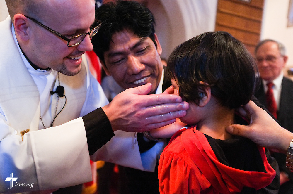 The Rev. Matthew Clark baptizes 21 Nepali immigrants, including Sweta Gurung, on Sunday, Jan. 12, 2014, at Ascension Lutheran Church in St. Louis, Mo. LCMS Communications/Erik M. Lunsford