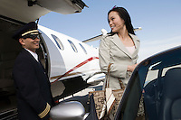 Mid-adult businesswoman turning back on pilot and smiling.
