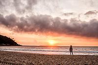 Mulher olhando o nascer do sol  na Praia de Quatro Ilhas. Bombinhas, Santa Catarina, Brasil. / <br /> Woman looking at the sunrise at Quatro Ilhas Beach. Bombinhas, Santa Catarina, Brazil.