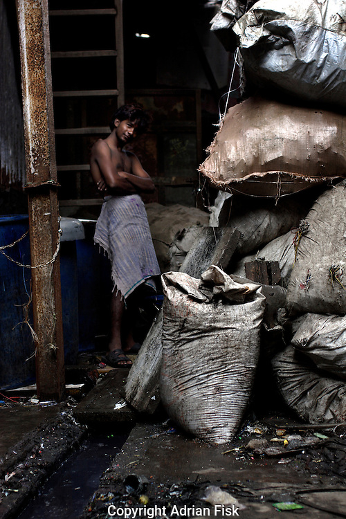 A boy pauses from his work of sorting bags of plastic waste on 21st Oct 2006.