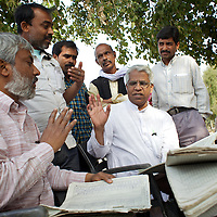 Rupesh (sitting, left) and his colleague Father Jose Kariakatt (centre, sitting), of the PUCL (People's Union for Cilvil Liberties) monitoring the right to food,  check administration records for the midday meals program at the Madhya Vidayalaya school in Tetua village. Teachers and local residents gather around...In the course of his work, Rupesh (no surname), advisor to the Indian Supreme Court Commissioner on the right to food, made an unannounced visit to Madhya Vidayalaya school in Tetua village. Such checks are an important way of holding local administrations to account and properly enforcing schemes like the school midday meals program. Unfortunately, a lack of resources mean that visits by Rupesh and his colleagues are rare...Rupesh found that meals at the Madhya Vidayalaya school had been suspended five days earlier because the Bihar state government had failed to deliver supplies to the school. Rupesh also discovered that cooking utensils had been stolen from a store cupboard. Such examples of lax supervision of fundamental programs are commonplace in much of rural north India where administrations have little personal vested interest in the proper running of schemes that benefit only the poor. Rupesh argues that the only way to properly administer schemes like school midday meals is to make them universal so that the the educated middle class, and not just the poor, have a personal interest in them...Rupesh is supported by Oxfam as part of a five month pilot program that began in November 2010...Photo: Tom Pietrasik.Tetua village, Gaya District, Bihar. India.February 24th 2011