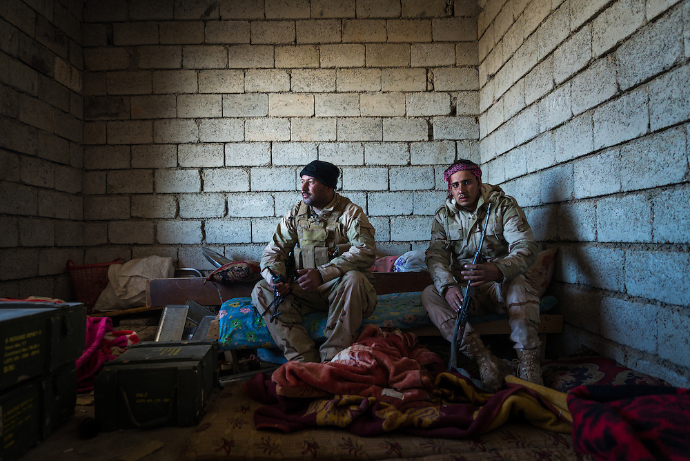 Iraqi soldiers take cover from Islamic State sniper fire inside an abandoned house in the village of Ganus Al Ulya, south of Mosul, on December 7, 2016.