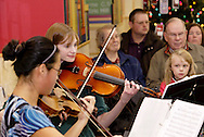 Barbara & Bob Prim of Washington Township and Amelia Campbell, 5 of Centerville watch Centerville High School Orchestra members Run Wei Wang (left) and Caroline Danzi perform holiday music at the WashingtonCenterville Public Library in Centerville, Monday, December 5, 2011.