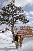 Two hikers explore Bryce Canyon in Winter snow.