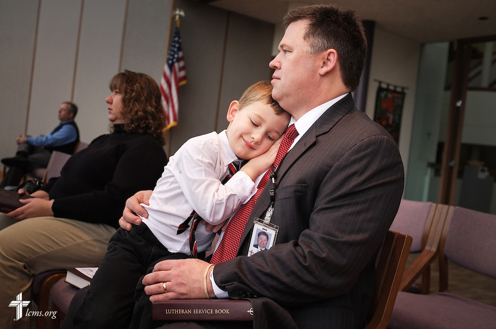 Mark Hofman, executive director of LCMS Mission Advancement, snuggles his 4-year-old son Matthew during morning chapel service at the LCMS International Center on Friday, Dec. 13, 2013, in Kirkwood, Mo. His wife Rachel (left), sits next to them. LCMS Communications/Erik M. Lunsford
