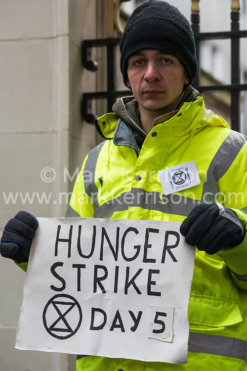 London, UK. 22 November, 2019. A climate activist from Extinction Rebellion stands outside the headquarters of the Conservative Party on the fifth day of an 'Election Rebellion' hunger strike to highlight government inaction on the climate and ecological emergency. Activists are also present outside the headquarters of other political parties during the general election.