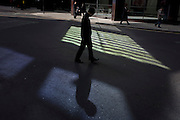 A downcast male pedestrian walks through reflected light shining from a City of London office building.