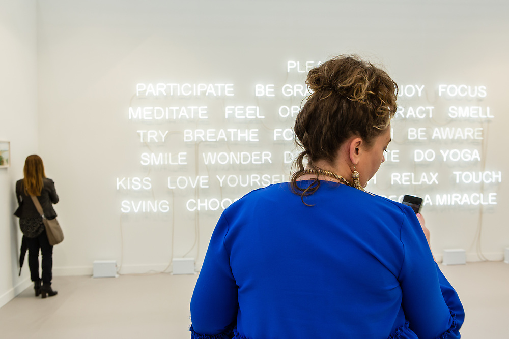 "New York, NY - 5 May 2017. The opening day of the Frieze Art Fair, showcasing modern and contemporary art presented by galleries from around the world, on Randall's Island in New York City. A woman checks her phone in front of an installation of neon tubes by Jeppe Hein, ""Please Participate,"" in the 303 Gallery."