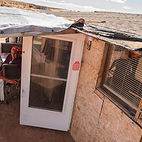 Julia Begay helps her grandmother Anna Begay prop open the front door of their home near Tonalea on the former Bennett Freeze Wednesday.