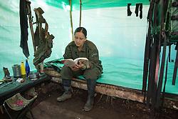 El Diamante, Meta, Colombia - 15.09.2016        <br /> <br /> A guerilla  fighter is reading a book in her sleeping booth. Guerilla camp during the 10th conference of the marxist FARC-EP in El Diamante, a Guerilla controlled area in the Colombian district Meta. Few days ahead of the peace contract passing after 52 years of war with the Colombian Governement wants the FARC decide on the 7-days long conferce their transformation into a unarmed political organization. <br /> <br /> Eine Kaempferin liest ein Buch in ihrem kleinen Unterschlupf. Guerilla-Camps zur zehnten Konferenz der marxistischen FARC-EP in El Diamante, einem von der Guerilla kontrollierten Gebiet im kolumbianischen Region Meta. Wenige Tage vor der geplanten Verabschiedung eines Friedensvertrags nach 52 Jahren Krieg mit der kolumbianischen Regierung will die FARC auf ihrer sieben taegigen Konferenz die Umwandlung in eine unbewaffneten politischen Organisation beschlieflen. <br />  <br /> Photo: Bjoern Kietzmann