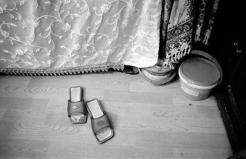A pair of slippers and a pot of wax on the floor of a private beauty salon. Tehran, Iran, 2007