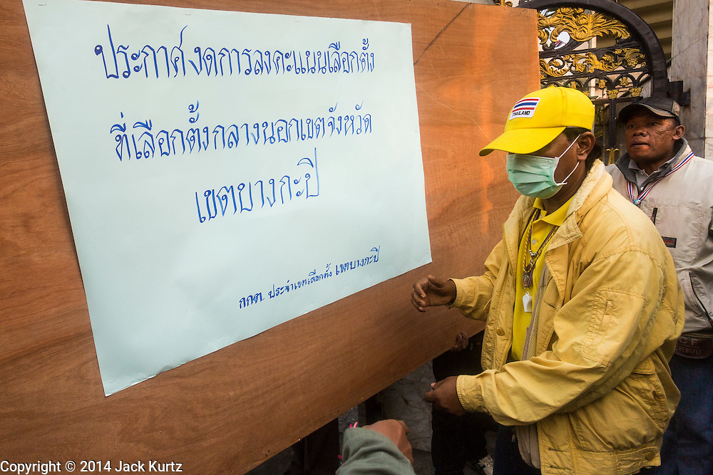 26 JANUARY 2014 - BANGKOK, THAILAND:  Anti-government protestors move a barricade into place announcing the closure of the polling place at Bang Kapi School. Anti-government protestors forced the closure of polling places in Bangkok Sunday as a part of Shutdown Bangkok. Early voting was supposed to be Sunday January 26 but blocked polling places left hundreds of thousands of people unable to vote casting the February 2 general election into doubt and further gridlocking Thai politics. Protestors blocked access to gates and entry ways to polling places and election officials chose the close them rather than confront protestors. Shutdown Bangkok has been going for 12 days with no resolution in sight. Suthep, the leader of the anti-government protests and the People's Democratic Reform Committee (PDRC), the umbrella organization of the protests,  is still demanding the caretaker government of Prime Minister Yingluck Shinawatra resign, the PM says she won't resign and intends to go ahead with the election.   PHOTO BY JACK KURTZ
