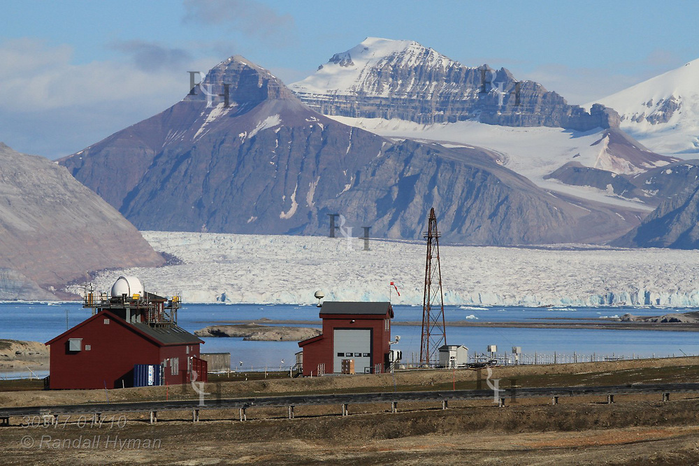 Distant glaciers loom at far end of Kongsfjorden behind French-German AWIPEV research station in July at Ny-Alesund; Svalbard, Norway.