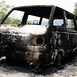 Smouldering Indian taxi van ambushed and burned out in terrorist attack in Manipur state close to the Myanmar border