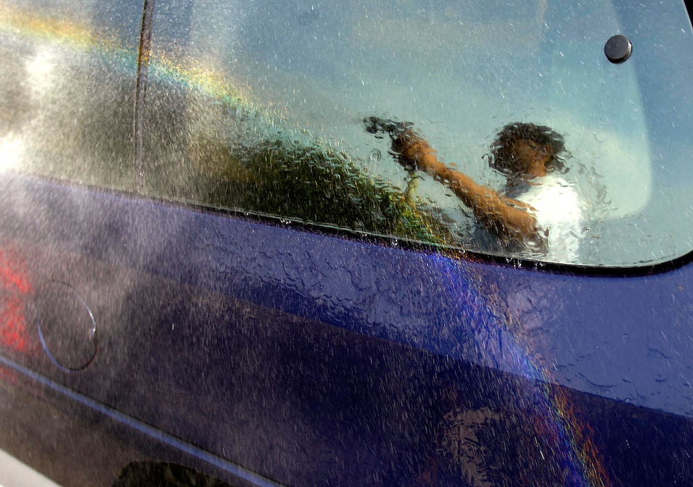 (COMMUNITY) Wall Twp/ 7/19/2003   Alex Ortiz of Jackson rinses off a car and makes a rainbow at the same time during a  free car wash held at the Full Gospel Church in Wall Twp.  Michael J. Treola Staff Photographer..MJT