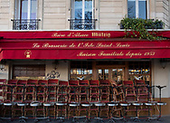 Tables and chairs stacked outside a brasserie early in the morning on the Il de St Louis, Paris, France, Europe