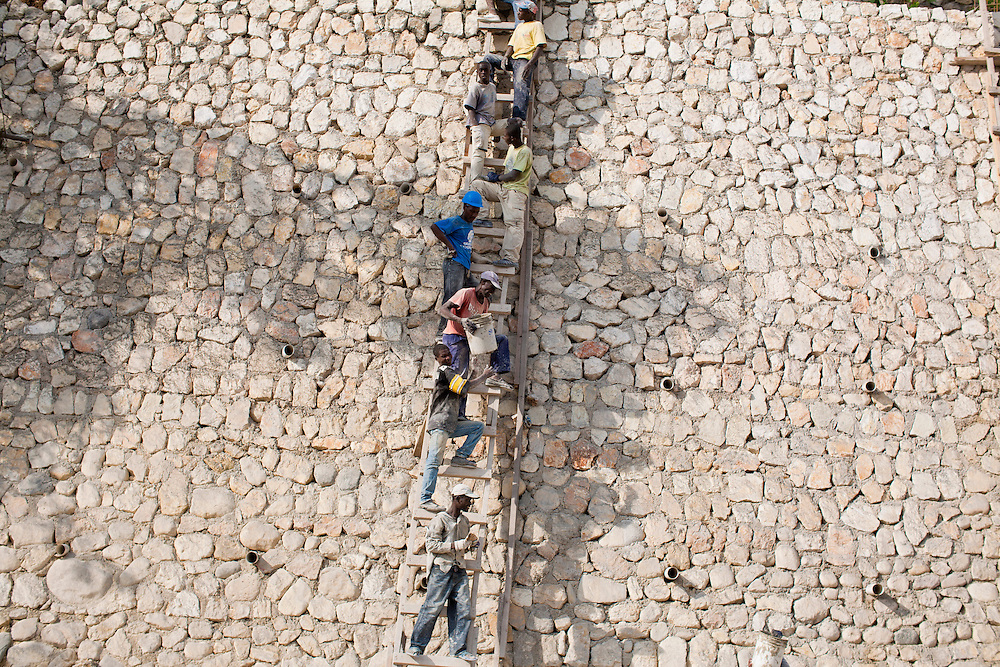 Men transport cement to the top of a retaining wall up a ladder with buckets below the destroyed Hotel Montana on July 6, 2010 in Port-au-Prince, Haiti.