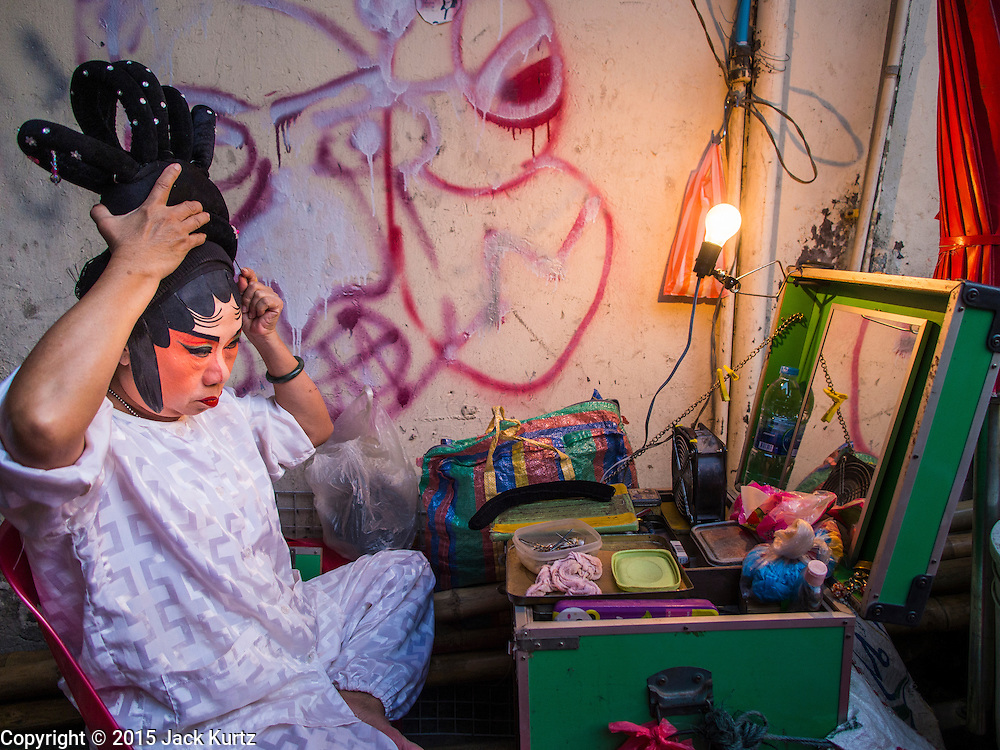 16 JANUARY 2015 - BANGKOK, THAILAND:  A performer with the Sai Yong Hong Teochew Opera Troupe puts on her make up before performing at the Chaomae Thapthim Shrine, a Chinese shrine in a working class neighborhood of Bangkok near the Chulalongkorn University campus. They don't have dressing rooms per se, instead setting up their make up tables right on the sidewalk. The troupe's nine night performance at the shrine is an annual tradition and is the start of the Lunar New Year celebrations in the neighborhood. Lunar New Year, also called Chinese New Year, is officially February 19 this year. Teochew opera is a form of Chinese opera that is popular in Thailand and Malaysia.   PHOTO BY JACK KURTZ