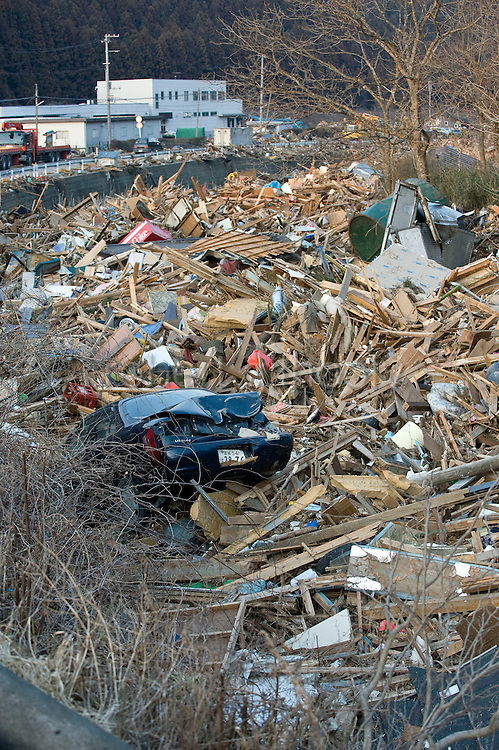 A car is among the pieces of broken homes and other debris that was swept inland by the tsunami that followed the March 11 magnitude 9 quake in Minami Sanriku Town, Miyagi Prefecture, Japan on 13 March, 2011. Some 10,000 people out of the coastal town's population of  17,666 are reported as missing  following the 10-meter-high wave that struck the village.. Photographer: Robert Gilhooly