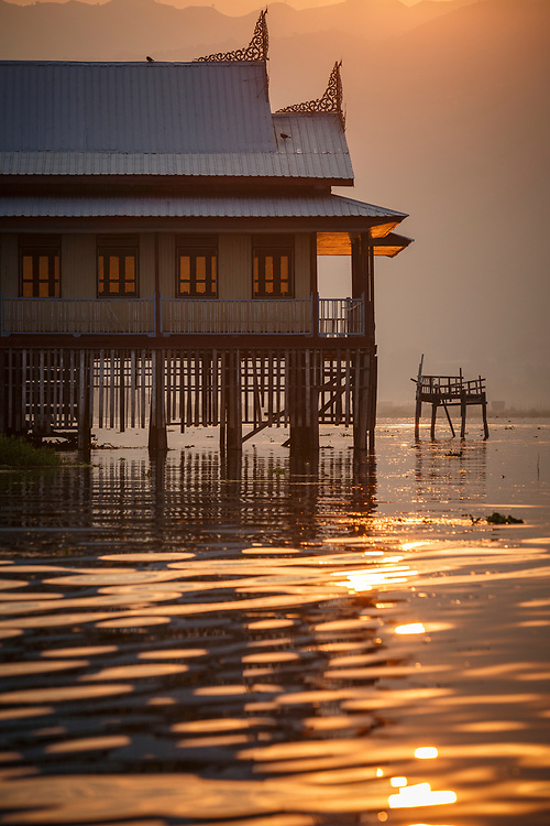 The glow from the morning sun reflected across the lake around the stilts of a hotel mid-lake.