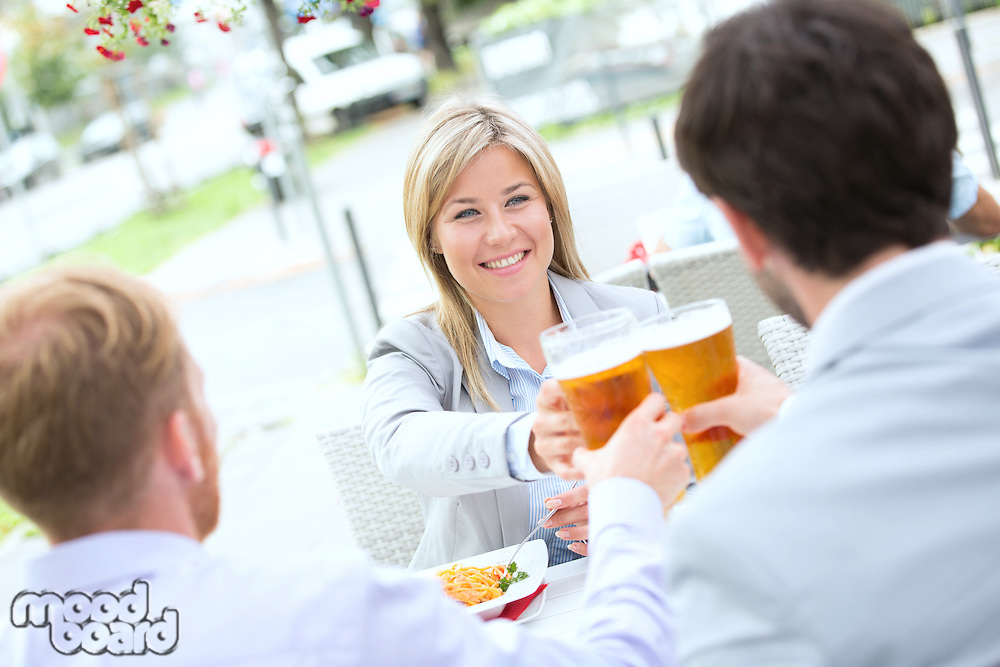Happy businesswoman toasting beer glass with male colleagues at sidewalk cafe