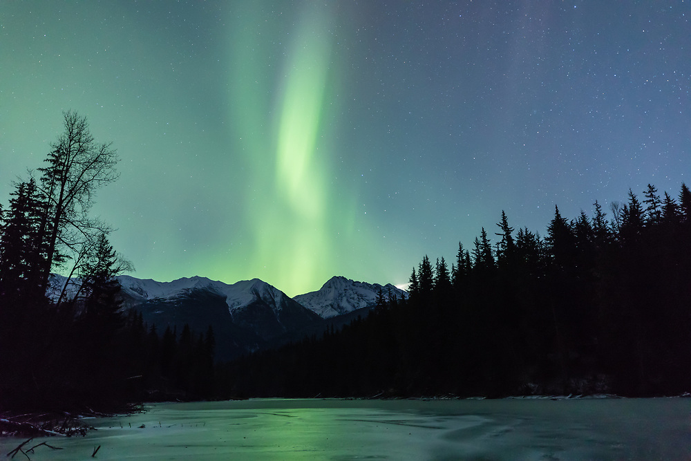 The aurora borealis over Mosquito Lake near Haines in Southeast Alaska. Winter. Evening.