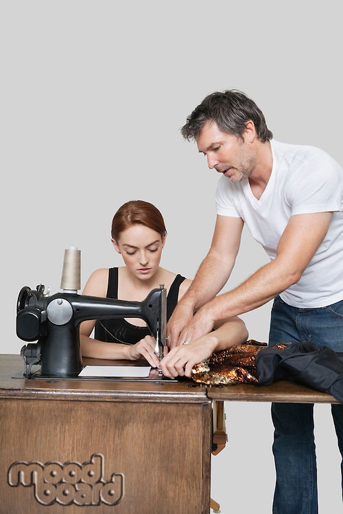 Designer helping coworker in stitching cloth on sewing machine over colored background