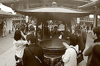Mar 6, 2006; Tokyo, JPN; Asakusa.Visitors gather around a large bronze incense bowl in front of the Senso-ji Buddhist temple and waft the smoke (considered to be the breath of the gods) upon themselves for its supposed curative powers...Photo credit:  Darrell Miho
