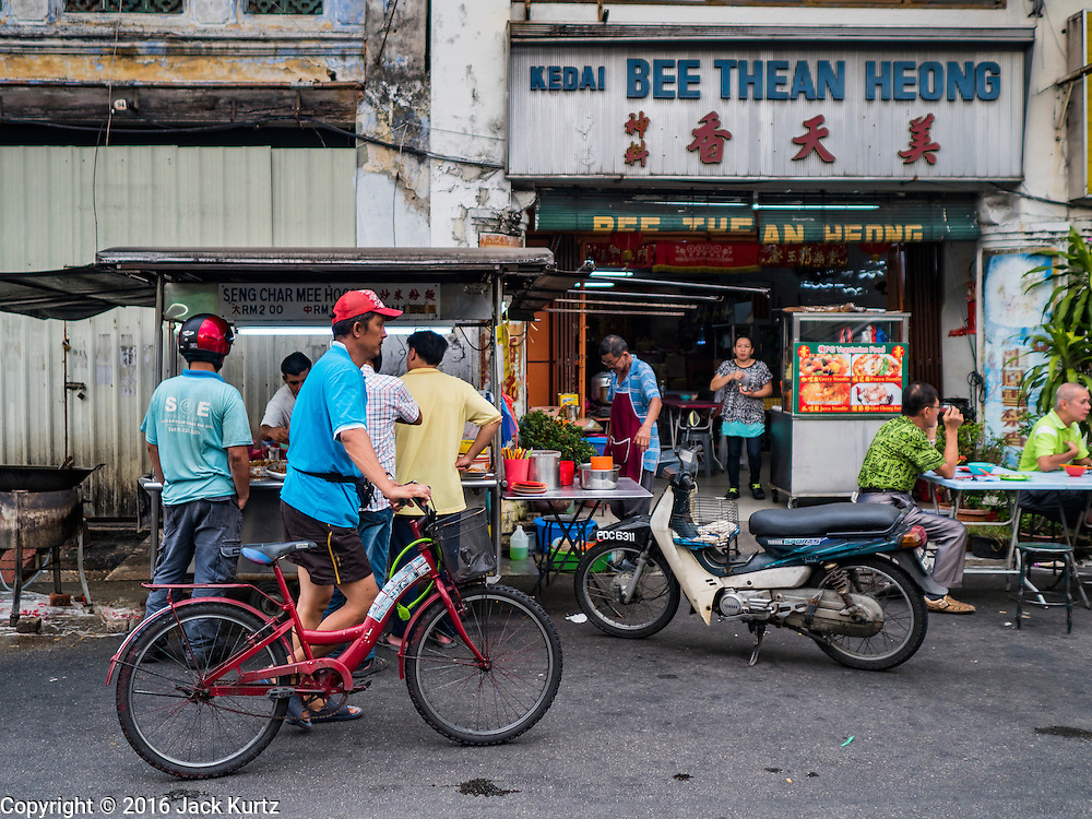 "15 NOVEMBER 2016 - GEORGE TOWN, PENANG, MALAYSIA: A man pushes his bike past a food stall on Kimberly Street, one of George Town's better known ""food streets."" George Town is a UNESCO World Heritage city and wrestles with maintaining its traditional lifestyle and mass tourism.           PHOTO BY JACK KURTZ"
