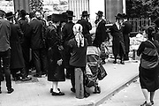 A husband, his wife sit by the line to purchase bus tickets from Jerusalem to Meron to visit Rabbi Simeon Bar Yochai's grave for the festivity of Lag BaO'mer.