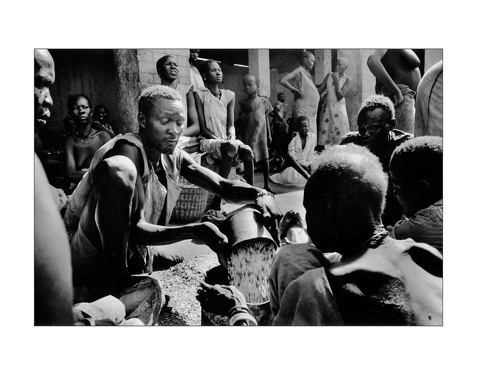 A man distributes donated  grain at a refugee distribution site in Wau, Sudan.  1989 &copy;Ed Hille/ Picturedesk.Net / The Philadelphia Inquirer (keywords: africa;hunger; starvation) <br /> ONE TIME USE ONLY