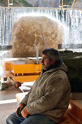 Covid 19 - Stonemason Justin Warren resting in preparation for creating the many new headstones required as a consequence of the mounting Coronavirus death toll, one of an increasing daily number (9 that day) being ordered from a Purbeck stone quarry at St Aldhelm's head Dorset UK April 2020