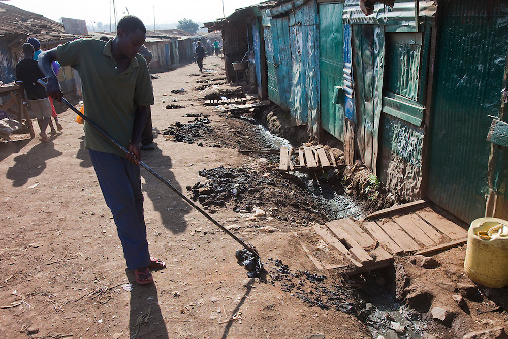 A man rakes muck out of open sewer outside microloan beneficiary Roseline Amondi's small restaurant in the Kibera slum, Nairobi, Kenya. (Roseline Amondi is featured in the book What I Eat: Around the World in 80 Diets.) The raking of muck raises the level of the street over time.  Trash is also burned in the dirt street, as the streets and alley are too narrow for garbage collection, and even fire engines, raising the risk of huge slum fires. Kibera is Africa's biggest slum with nearly one million inhabitants.